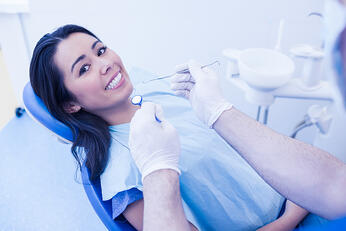 Dentist examining smiling female patient at dental clinic