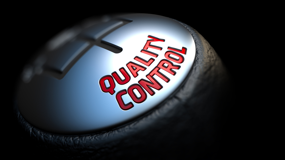 Quality Control - Red Text on Cars Shift Knob on Black Background. Close Up View. Selective Focus.